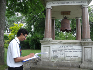 Secondary school pupil studying a war memorial © S Lemieux, 2012