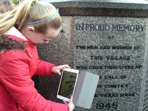 Year 6 pupil from Hollingworth Primary School taking a photograph of Hollingworth war memorial while carrying out a condition survey © War Memorials Trust, 2018