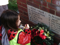 Key stage 2 pupil from Great Witchingham C of E Primary Academy looking at names on Great Witchingham war memorial © War Memorials Trust, 2018